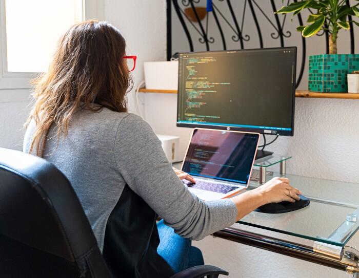 María Garvía está de espaldas trabajando en el ordenador. Ella está sentada en una silla negra de despacho. La mesa es de cristal y tiene un ordenador y una pantalla. Ella está de espaldas con un jersey gris y negro, la mano derecha con el ratón. Detrás de la mesa hay una estantería que es como una barandilla. Está en una habitación de color blanco que tiene una ventana.