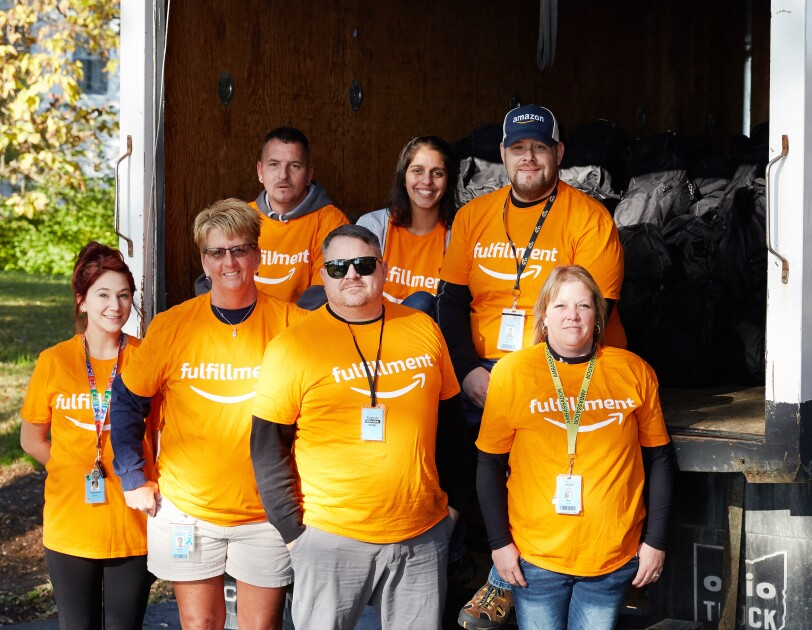 Amazon Fulfillment associates gathered to stuff backpacks with essentials