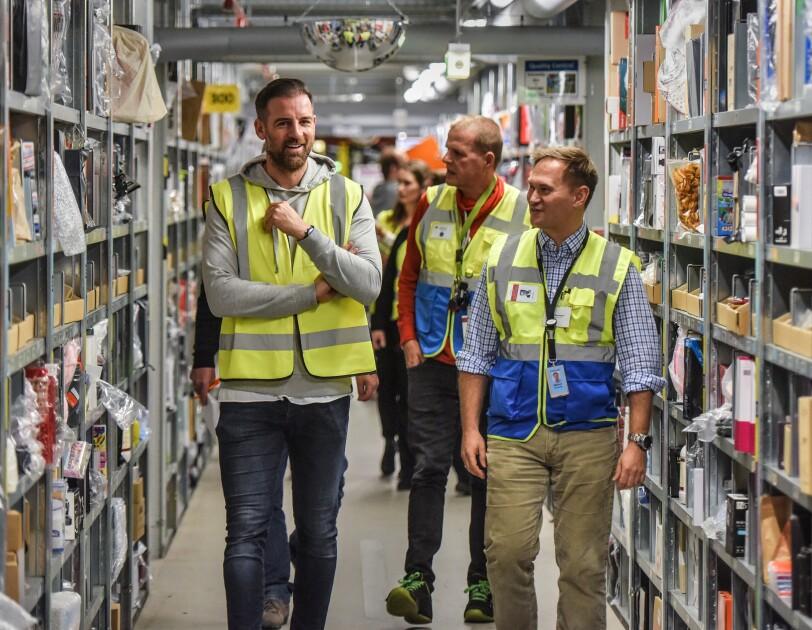 Christoph Metzelder läuft mit Mitarbeitern von  Amazon durch einen Regalgang des Logistikzentrums.