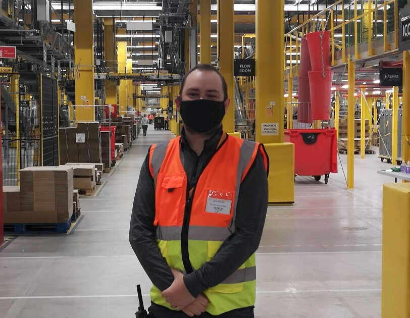 Liam Fletcher, WHS Coordinator at Amazon's fulfilment centre in Warrington, pictured wearing a high visibility vest and face mask.
