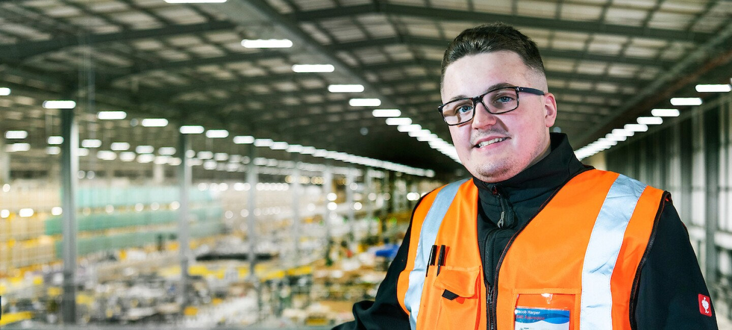 Apprentice, Jacob Harper, pictured on a balcony overlooking the inside of an Amazon fulfilment centre, smiling at the camera.
