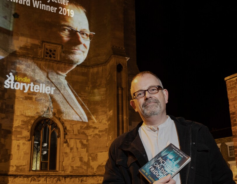 Ian W. Sainsbury holding his book in front of a Storyteller projection of his head shot congratulating him on his award.
