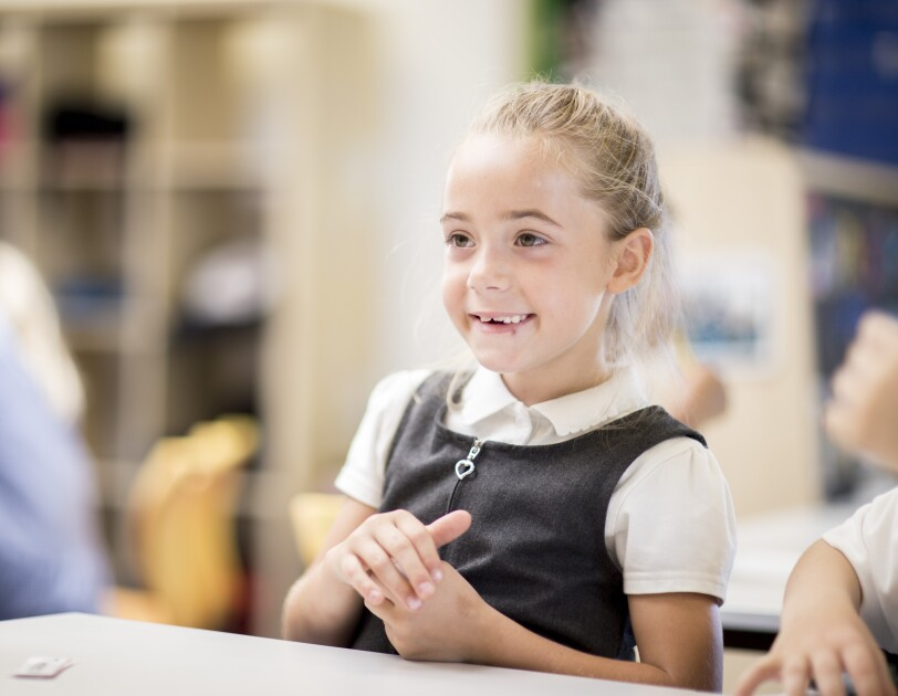 A primary school child sitting at a desk in a classroom at school.