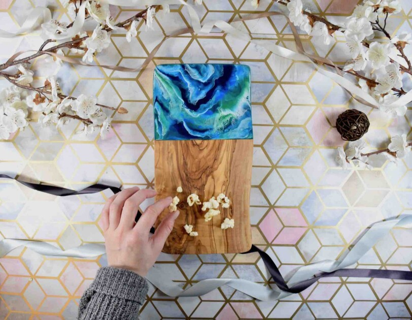 Birds-eye view of someone picking up popcorn from a Kate Chesters Resin Board, There are decorative flowers and ribbons surrounding the board.