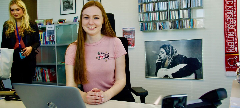 Eine junge Frau in rosa T-Shirt sitzt an einem Schreibtisch, vor ihr ein Laptop