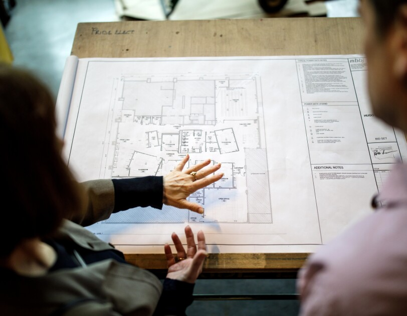 A woman and a man look down at blueprints at a construction site.