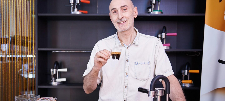 Nino Santoro, l'inventore di Kamira, regge una tazzina di espresso e mostra orgoglioso la sua macchina accanto a una brocca d'acqua e un vaso di polvere di caffé