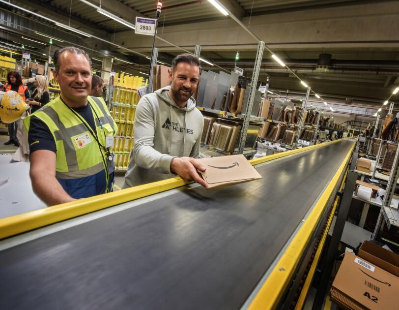 Christoph Metzelder legt ein frisch verpacktes Amazon Päckchen auf das Fließband im Logistikzentrum. Links von ihm steht Karsten Frost. Beide grinsen in die Kamera.