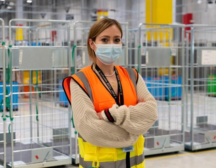 Donna ripresa a mezzo busto all'interno di un magazzino Amazon. La donna è biona, indossa una mascherina chirurgica sul volto, un giubbino catarinfrangente e un maglione color senape.