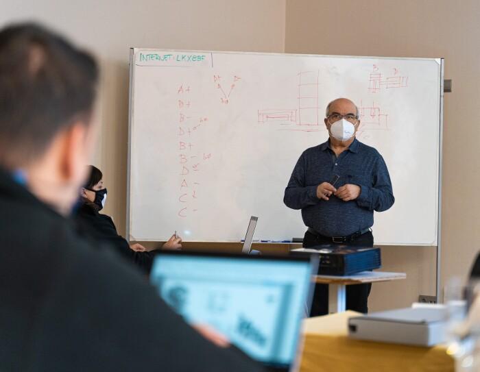 El programa Aprendizaje de Amazon tiene una parte teórica y otra práctica. En una aula y con una pizarra de rotulador y con una pantalla de ordenador proyectada a la pared, hay un profesor vestido con camisa azul, pantalones tejanos y un bolígrafo en la mano explicando teoría delante de la pizarra. Desenfocados se ven tres estudiantes sentados delante de sus ordenadores.