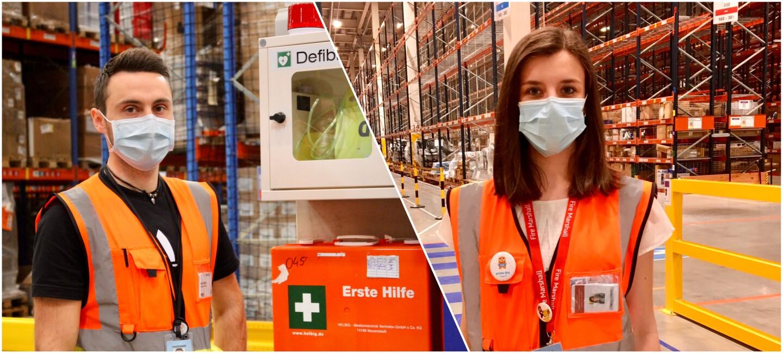 Portrait einer jungen Frau und eines jungen Mannes: Beide tragen Sicherheitswesten und Masken und befinden sich in einem Logistikzentrum.