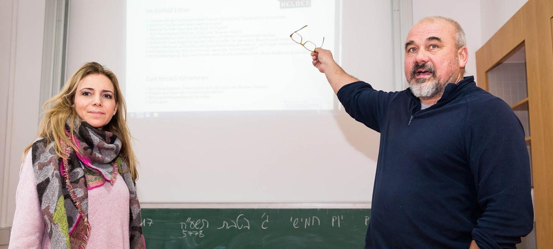 Ein Mann und eine Frau stehen vor einer Wand, auf der eine Präsentation läuft. Sie schauen in die Kamera. Der Mann zeigt mit seiner Hand auf die Präsentation hinter sich.
