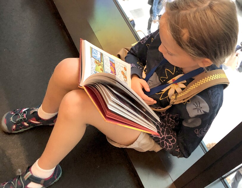 A girl sits against a window reading a book.