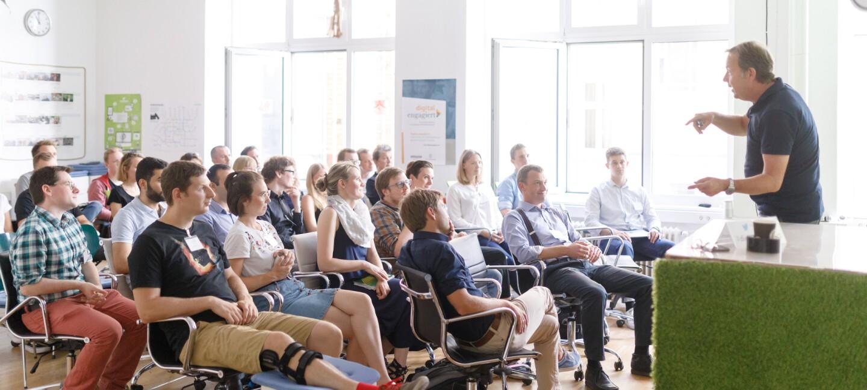 Ralf Kleber steht auf einer kleinen Bühne und hält einen Vortrag zu digital.engagiert.
