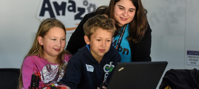 2 Kinder am PC, im Hintergrund sieht man eine Betreuerin, die ebenfalls in den Laptop blickt.