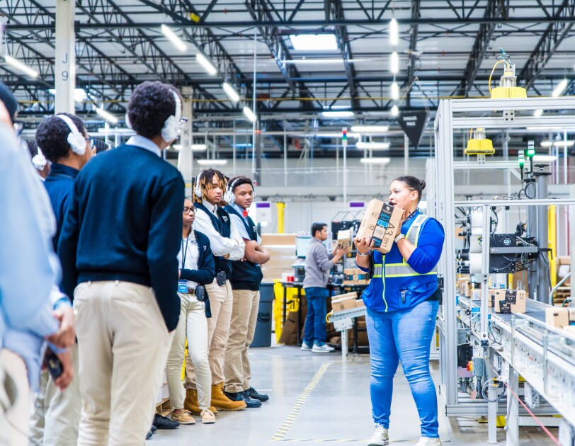 Students in school uniforms stand in a large warehouse space and look on as a woman holding an Amazon box makes a presentation.