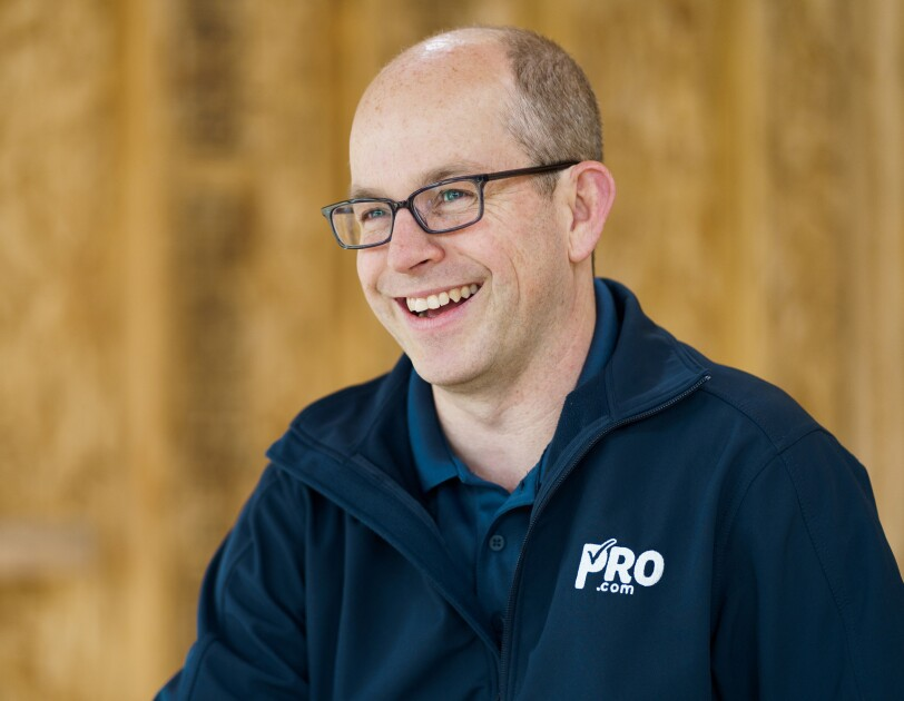 "A man wearing a navy polo short with ""Pro.com"" embroidered on it, smiles. Behind him a home construction project."