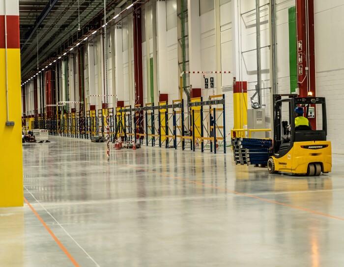 Toro mecánico de construcción de color amarillo. El toro está situado en un pasillo en el que se ven otros elementos de construcción.