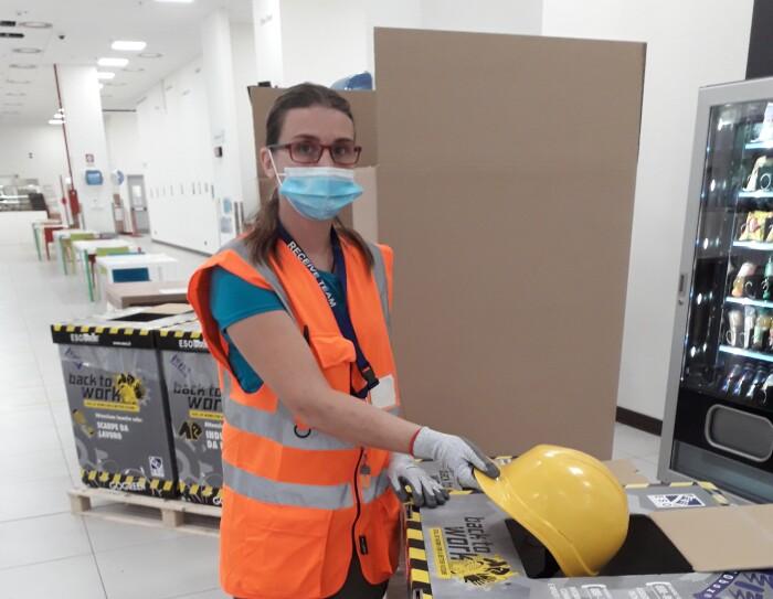 Un'operatrice di magazzino sta introducendo un caschetto da lavoro giallo all'interno di una scatola dedicata al riciclo degli indumenti da lavoro.