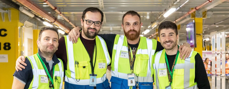 Quattro uomini guardano in camera e indossano gilet ad alta visibilità all'interno del centro di distribuzione Amazon di Passo Corese.