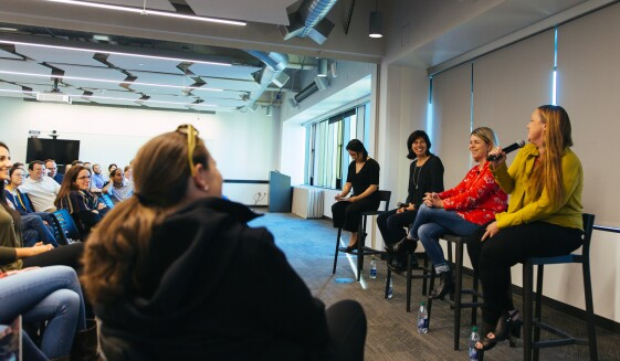 Four women are seated at the front of a conference room, leading a panel on leadership. Each is seated on a raised bar-height stool. In front of them, Dozens of Amazonians face them, as they speak.