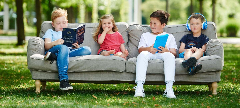 Kinder sitzen im Freien auf einer Couch und lesen Märchen