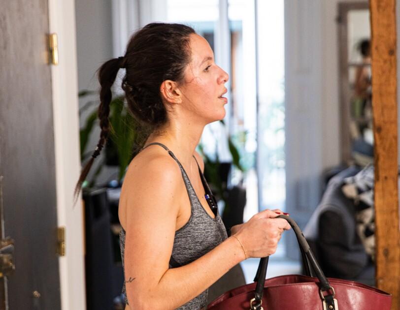 Maria Jover es una joven amazonian que lleva una trenza de pelo negro. Va vestida con sujetador deportivo y unas mallas de color gris y unas deportivas negras. Lleva las uñas pintadas de color rojo.  En su casa se ve la puerta de entrada y el sofá. Ella está haciendo deporte sujetando un bolso rojo con las dos manos.