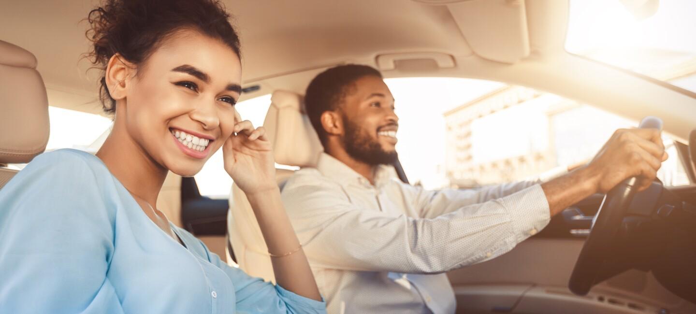 Ein Mann und eine Frau sitzen in einem Auto und lachen. Der Mann sitzt am Steuern und fährt den Wagen.