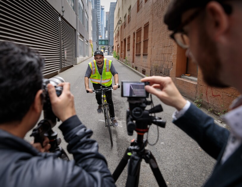 Two men in the foreground point cameras at a man on a bicycle who is riding toward them. The man on the bicycle wears a fluorescent safety vest. Buildings rise up on the right and left side of the image, and an alley stretches out behind the cyclist.