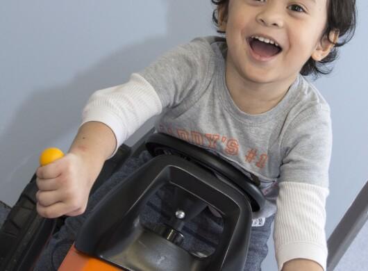 Ein ca. 3 Jahre alter Jungen auf einem Kinderbagger.