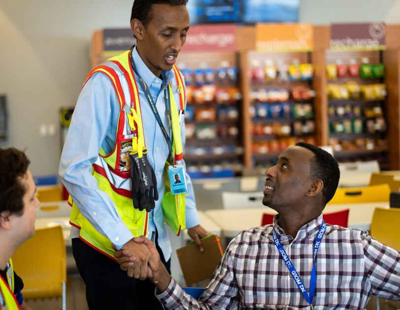 Two men shake hands while a third man looks on. Two of the men are wearing brightly colored safety vests.