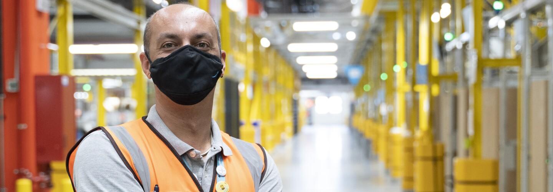 Una foto a mezzo busto di Oreste Tagliaferri con alle spalle il corridoio di un centro logistico di Amazon. Oreste indossa una mascherina nera in tessuto, un giubbino di sicurezza. Ha le braccia conserte e sul suo braccio destro si intravede un tatuaggio.