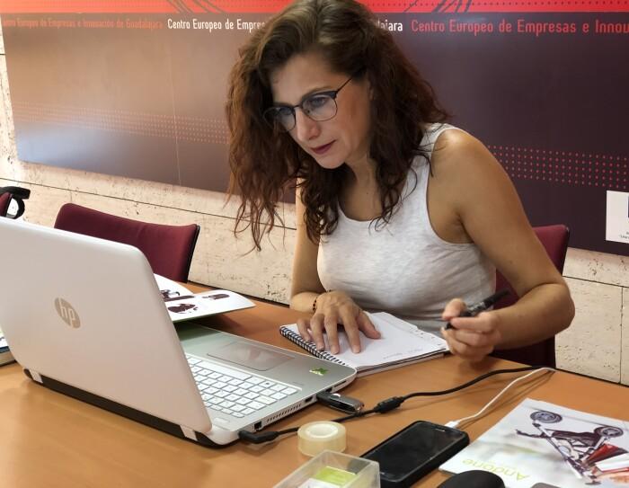 Irene, creado de Andone Dynamic Walks, sentada en una mesa y trabajando delante del ordenador. Viste con una camiseta sin mangas blanca y lleva gafas. Mira atentamente el ordenador y en la mano izquierda tiene un bolígrafo con el que escribe en un papel.