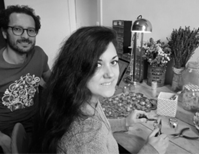 Les deux fondateurs de Trois Fenêtres se tiennent devant une table où est posé du matériel de création artisanale ainsi qu'une lampe et des bouquets de fleurs. C'est une photo noir et blanc.