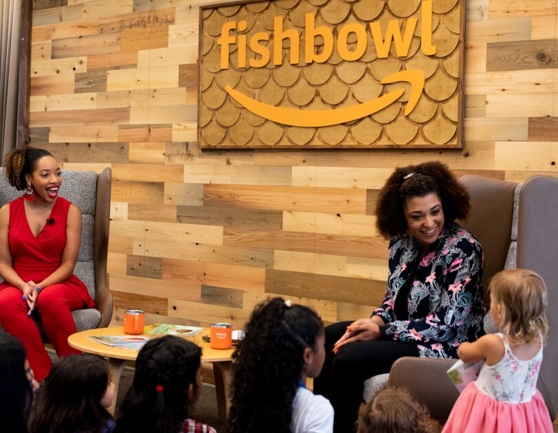 Two women sit in chairs in front of a small group of children.