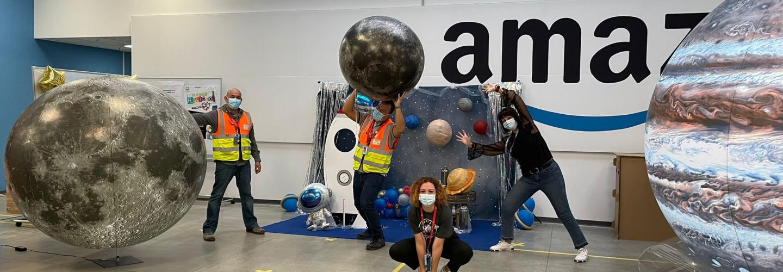 Gruppo di dipendenti Amazon posa in mezzo a riproduzioni di pianeti.