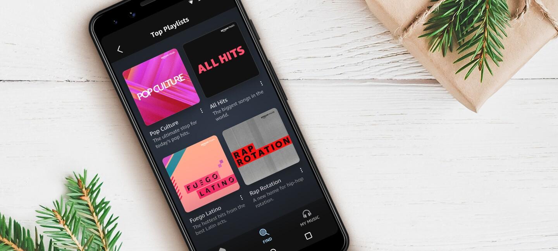 Ein Handy liegt auf dem Tisch und zeigt die Music App mit den neuesten Playlists.