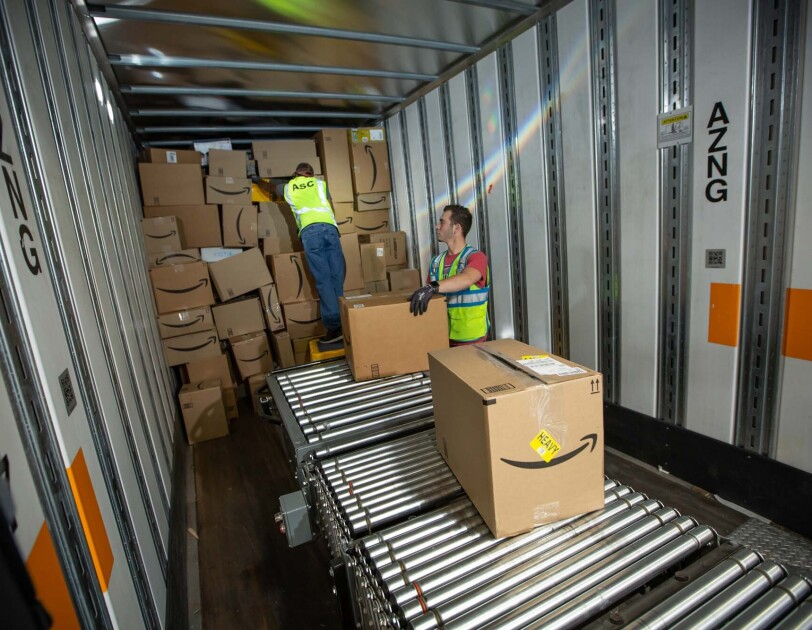 Two Amazon associates receive packages from a conveyor belt, as they prepare to place them on a trailer for distribution at a Columbus, Ohio fulfillment center, CMH2
