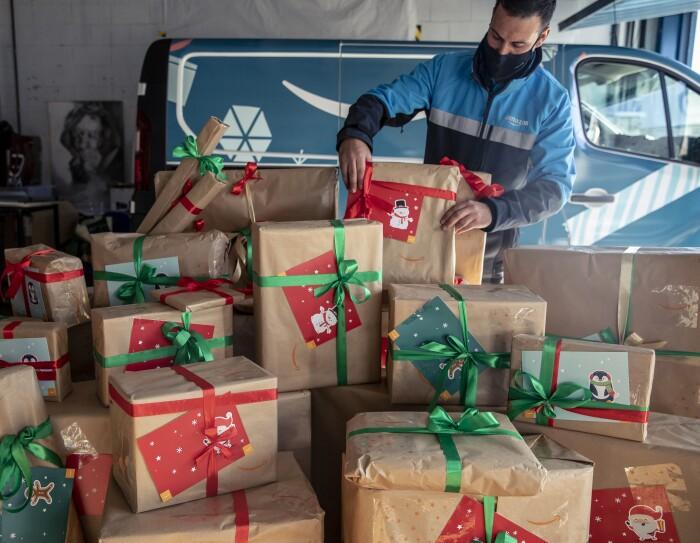 Centro de día para personas sin hogar Casablanca de Alcobendas. Una furgoneta de Amazon está dentro de un garaje. En segundo plano un conductor acabado de colocar una caja. El conductor va con una mascarilla negra y una chaqueta de Amazon azul claro, gris y azul marino. En primer plano paquetes de Amazon con lazos verdes y rojos y tarjetas regalo con motivos navideños.