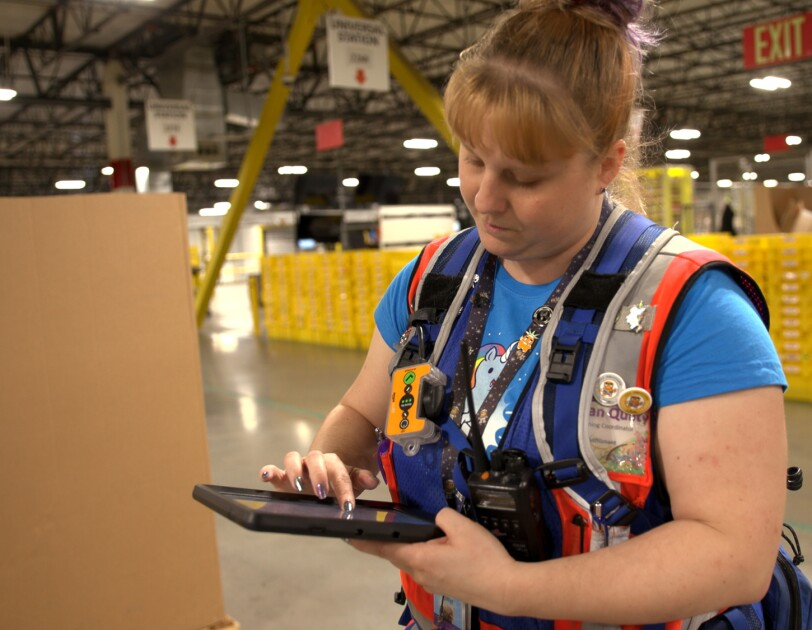 A woman in a safety vest works on a tablet device. She stands in a large warehouse space.