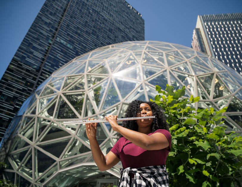 A woman plays the flute in front of a rounded glass-and-metal building.
