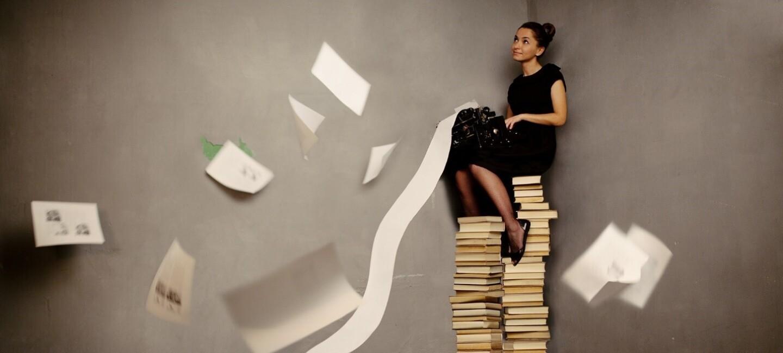 Eine Frau sitzt auf einem Stapel Bücher und schreibt auf einer Schreibmaschine ein Buch.