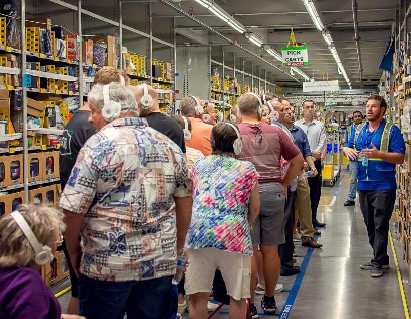 """A man in a safety vest stands next to a single-file line of people wearing white headphones. A hanging sign overhead says """"PICK CARTS."""""""