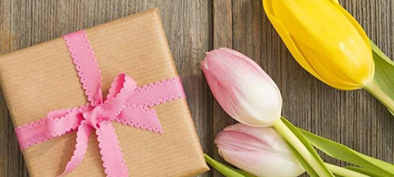 Un petit paquet enveloppé de papier craft avec un noeud rose et des fleurs roses et jaunes sont posés sur une table ou un plateau en bois