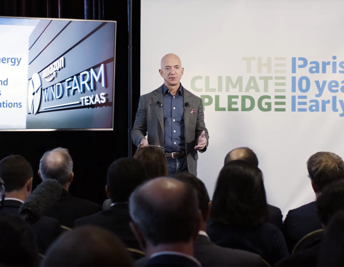"Jeff Bezos stands at the front of a room, in front of a display that shares data points about renewable energy at Amazon. Also behind him is the logo for ""The Climate Pledge."""