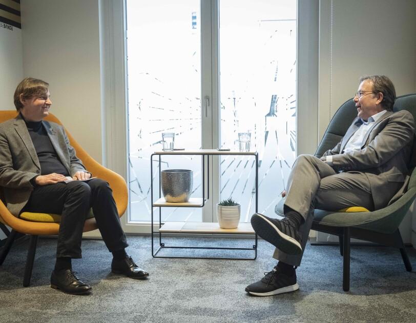 Zwei Männer sitzen auf Stühlen und schauen sich an.