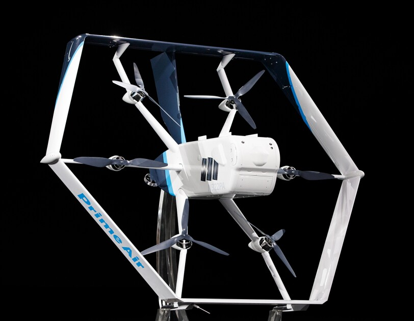 A white and light blue Prime Air drone in front of a black background. Six propellers and a main body are visible in the center of the drone.