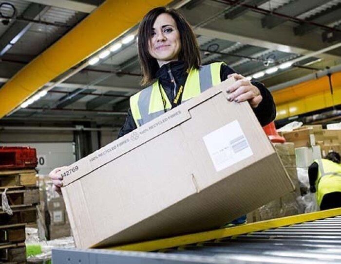 Amazon Mitarbeiterin stehe am Fließband und hat einen Karton in der Hand.