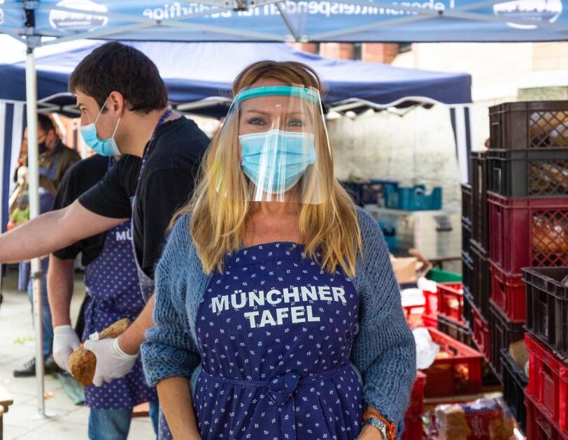Ehrenamtliche Helferin der Münchner Tafel mit blauer Schürze.