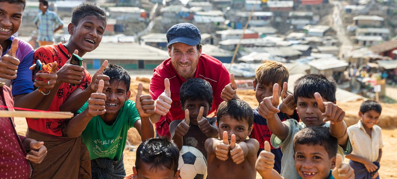 Ein Helfe der DRK steht mit einer Horde Kinder vor den Slums in Bangladesh. Alle zeigen den Daumen hoch und haben strahlende Gesichter.
